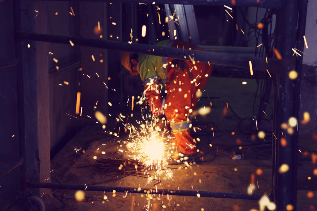 Construction worker drilling with sparks